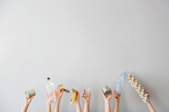 Hands with different types of garbage on white background