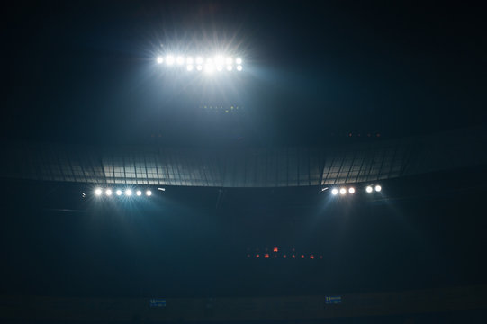 Stadium lights against dark night sky background. Soccer match lights.