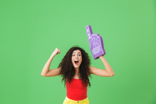 Portrait of modern woman 20s rejoicing and holding number one fan glove