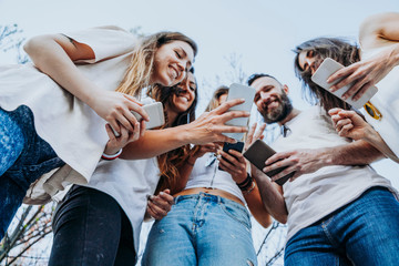 Group of five friends in the street with smartphone