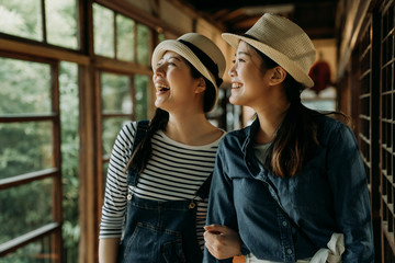 two asian female travelers in straw hats smiling laughing sightseeing spring garden view while walking in japanese wooden house walkway. happy cheerful women relaxing travel in tokyo japan lifestyle. Fototapete
