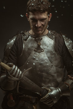 Emotional portrait of a young man in knight armor and a sword against a dark background.