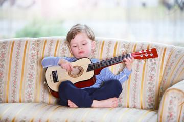Ein dreijähriger Junge spielt auf einer Gitarre