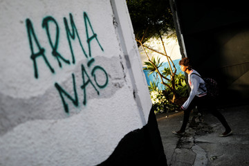 """A student arrives after classes resume at the entrance to Raul Brasil school, next a sign reading """"Weapons no"""", where the shooting took place, on the outskirts of Sao Paulo, in Suzano"""