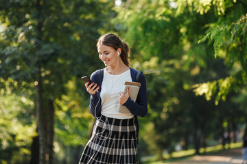 Cheerful young school girl walking outdoors
