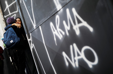 """A student embraces a teacher at the entrance to Raul Brasil school, next a sign reading """"Weapons no"""", where the shooting took place, on the outskirts of Sao Paulo, in Suzano"""