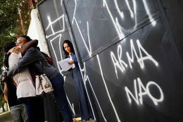 """A student embraces her mother in front of her teacher as she arrives after classes resume at the entrance to Raul Brasil school, next to a sign reading """"Weapons no"""", on the outskirts of Sao Paulo, in Suzano"""