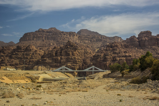 dry scenery wallpaper landscape of country side Middle East Jordan infrastructure bridge object with car road way along desert mountain ridge background