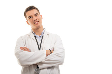 Portrait of young handsome doctor standing with arms crossed