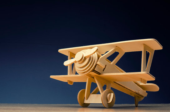 toy wooden retro airplane on wooden table background for travel  concept