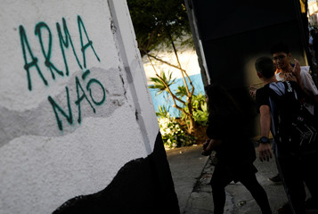 """Students arrive after classes resume at the entrance to Raul Brasil school, where the shooting took place, next a sign reading """"Weapons no"""", on the outskirts of Sao Paulo, in Suzano"""