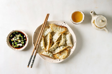 Fried asian dumplings Gyozas potstickers in white ceramic plate served with chopsticks, bowl of soy onion sauce, teapot over white marble background. Flat lay, space. Asian dinner