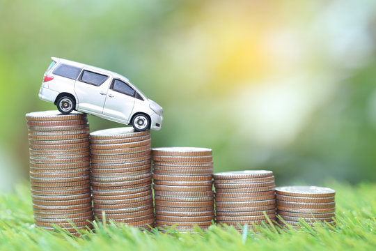 Miniature car model on stack of coins money on nature green background, Saving money for car, Finance and car loan, Investment and business concept.