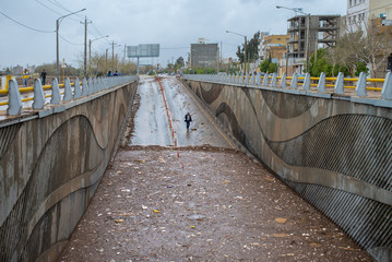 A man walks near a tunnel filled with water after a flash flooding in Shiraz