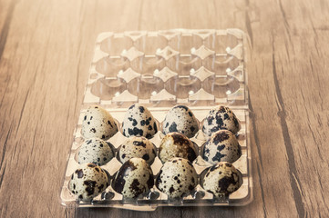 Quail eggs in plastic box on brown wooden background