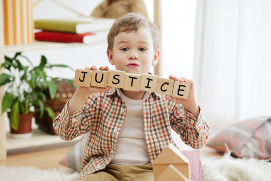 Wooden cubes with word justice in hands of little boy at home. Conceptual image about child rights, education, childhood and social problems.