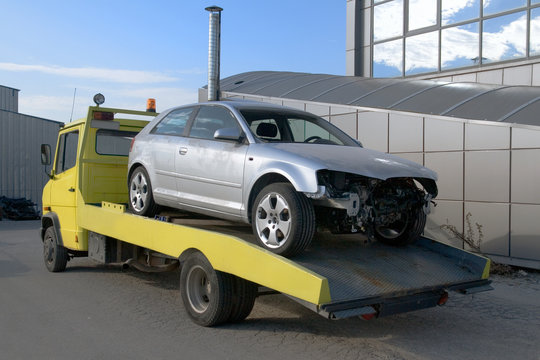 Damaged car after accident on tow truck