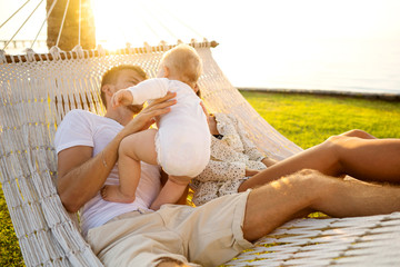 happy family on a tropical island at sunset lie in a hammock and play with their son
