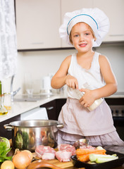 Little child in cook hat cooking soup