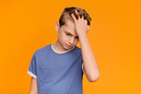 Upset boy holding his hand on head, suffering from headache