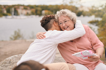 Grandson embracing smiling grandmother holding gift outdoors