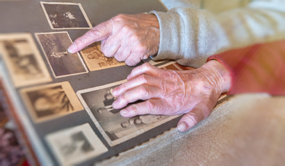 Elderly couple hands looking at old pictures album at home. Detail on hands and old images