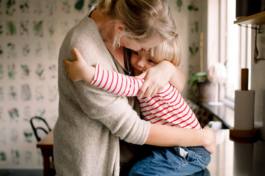 Mother embracing daughter in kitchen
