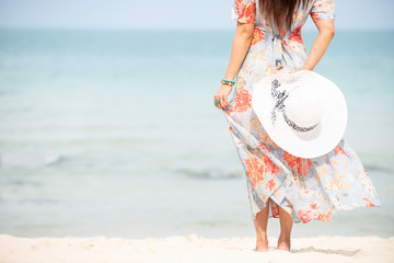 Relax traveler asia woman in dress holding sun hat standing on beach  enjoys her tropical  vacation