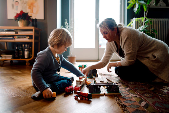 Mother and daughter playing with toy train in Livingroom