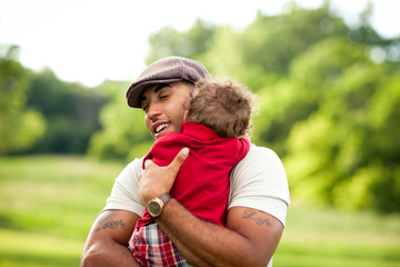Happy Father Hugging Toddler Son Outside - Color Portrait