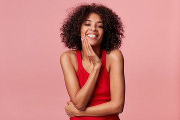 Happy pleased charming african american girl with afro hairstyle looks with pleasure, touches her face with palm, smiles, rejoices from soft skin, wearing red singlet, isolated on pink background