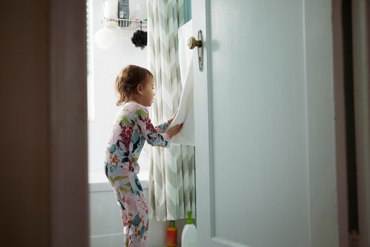 Side view of girl wiping hands with towel while standing in bathroom at home seen through doorway