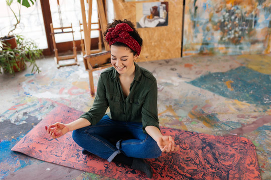 Young attractive smiling woman with closing eyes sitting on yoga mat in lotus pose and meditating while happily spending time in big cozy workshop with wood easel and modern paintings on background