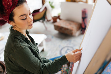Young serious woman with dark curly hair sitting on chair thoughtfully drawing picture on canvas in...