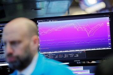 A chart is displayed behind a trader on the floor of the New York Stock Exchange (NYSE) shortly after the opening bell in New York