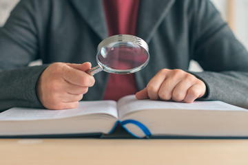 Businesswoman using magnifying glass to read the book