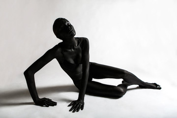 girl painted black paint lying on a white background