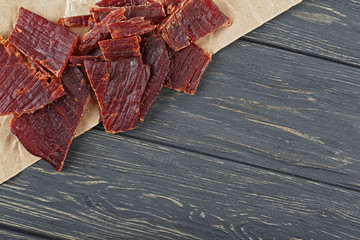 Beef jerky on a wooden board, close-up.