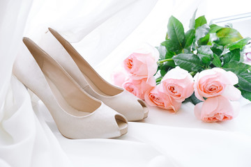 white women's bride shoes and a bouquet of pink roses lie on a white background of veils