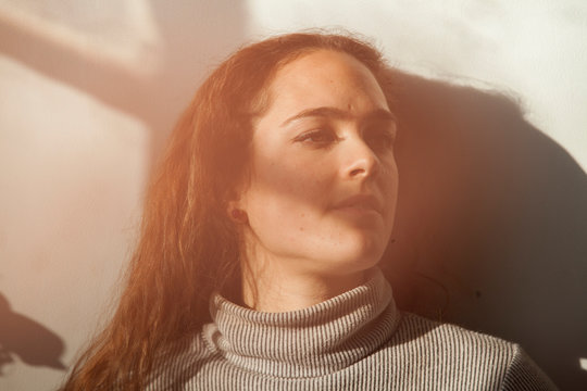 Young woman relaxing in sunlight at home
