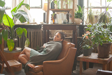 Side view of thoughtful woman wrapped in scarf looking away while relaxing on armchair by potted plants at home