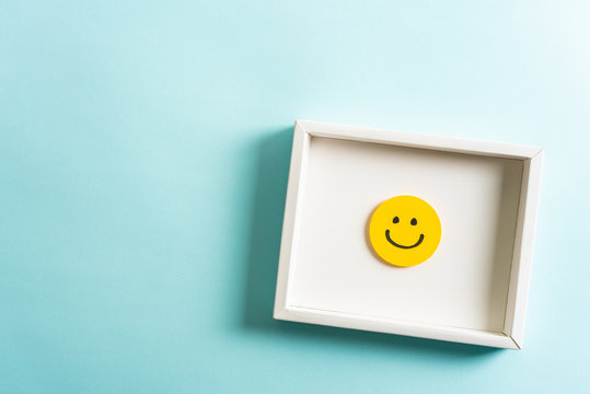 Concept of well done, feedback, employee recognition award. happy yellow smiling cartoon face frame on blue background.