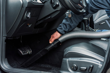 professionelle Autoreinigung in einer Werkstatt - Mann saugt den Innenraum eines Fahrzeuges_professional car cleaning in a garage - man vacuums the interior of a vehicle