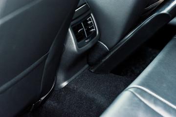 professionelle Autoreinigung in einer Werkstatt - Mann saugt den Innenraum eines Fahrzeuges_professional car cleaning in a garage - man vacuums the interior of a vehicle