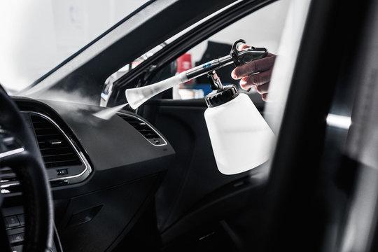 professionelle Autoreinigung in einer Werkstatt - Mann reinigt den Innenraum eines Fahrzeuges_professional car cleaning in a garage - man cleans the interior of a vehicle