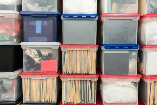 Stacked plastic file storage boxes with folders, binders and miscellaneous items.