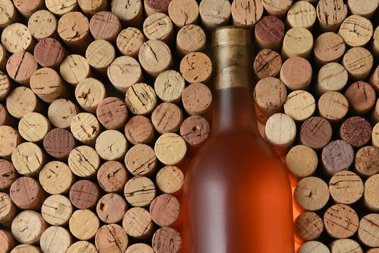 Closeup of a bottle of White Zinfandel wine surrounded by used corks