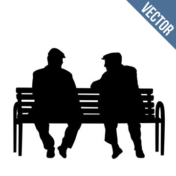 Two elderly people silhouettes sitting on a park bench