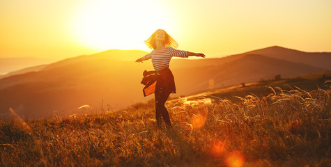 Happy woman jumping and enjoying life  at sunset in mountains. Wall mural