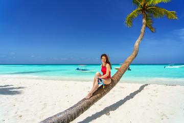 Young woman in bikini sitting on palm tree on the beach in Dominican Republic